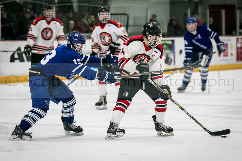 Spaulding's Shaun Cormier, right, looks to pass the puck while being defended by Merrimack's Regan Sedlar during Division II hockey action at the Rochester Ice Arena Saturday. [Photo by Scott Patterson/Fosters.com]