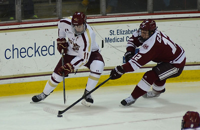 011813, Boston, MA - Boston College's Pat Mullane (11) struggles with UMass' Rocco Carzo (12) for control of the puck during Friday's game against UMass Amherst. Herald photo by Ryan Hutton