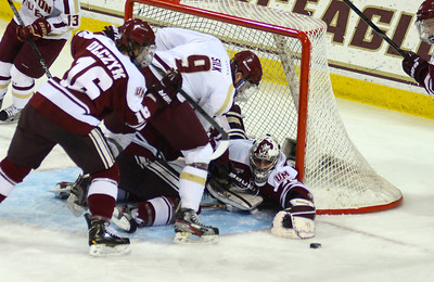 011813, Boston, MA - Boston College's Brendan Silk (9) tries to put the puck past UMass' Steve Mastalerz (39) as Eddie Olczyk (16) collides with both of them during Friday's game against UMass Amherst. Herald photo by Ryan Hutton