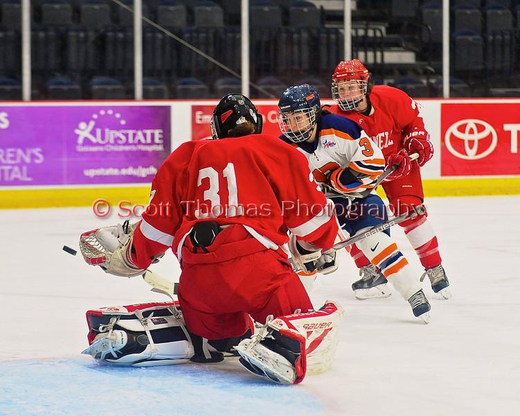 Syracuse University Orange Julie Knerr (3) has her shot blocked by Cornell Big Red goalie Paula Voorheis (31) in NCAA Women Ice Hockey action at the Onondaga County War Memorial on Tuesday, December 3, 2013.