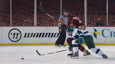 Jan. 13, 2012, Boston, MA - Norwich University Cadet Kyle Thomas, rear, and Babson College Beaver Cody Carlson, front, struggle to get to the puck during the two teams' Frozen Fenway game. By Ryan Hutton