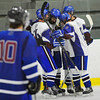Lunenburg/Ayer-Shirley's Kevin Cowdrey (2nd from left in group) celebrates his goal with teammates as Hopedale/Millis' Jake Munger skates by during Monday's game. The Lunenburg/Ayer-Shirley team won 5-0.<br /> SENTINEL & ENTERPRISE / BRETT CRAWFORD