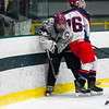Groton-Dunstable's Chris Lattini pushes the puck away from the boards as he is body checked by North Middlesex's Donnie Frederick. Nashoba Valley Voice/Ed Niser