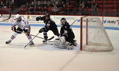 022313, Boston, MA - Northeastern's Mike McMurtry (7) fires a shot on Providence goaltender Jon Gilies (32) while Steven Shamanski (28) tries to stop him during the second period of Saturday night's game. Herald photo by Ryan Hutton