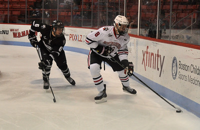 022313, Boston, MA - Northeastern's Adam Reid (8), tries to clear the puck from the boards as Providence's Tom Parisi (6) closes in during the first period of Saturday night's game. Herald photo by Ryan Hutton