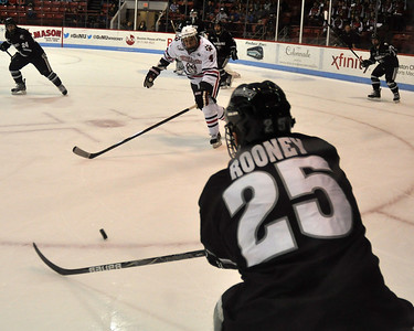 022313, Boston, MA - Northeastern's Dan Cornell (4) tries to grab the puck from Providence's Kevin Rooney (25) during the first period of Saturday night's game. Herald photo by Ryan Hutton