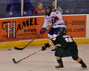 101212, Lowell, MA - Lowell's Stephen Buco puts the puck past Vermont's Pete Massar during the first period of Friday night's game. Herald photo by Ryan Hutton.