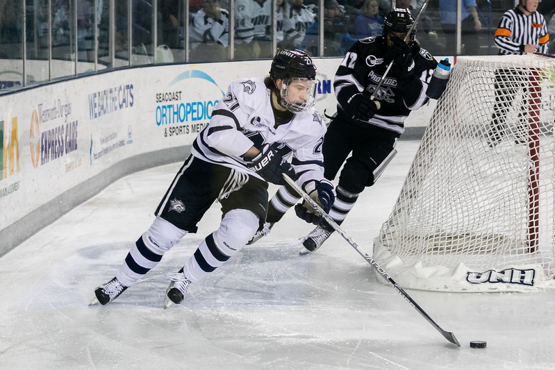 UNH's Matt Dawson, left, brings the puck out from behind the UNH net while being chased by Providence's Erik Foley, right, during Saturday's game at the Whittemore Center Arena in Durham. Photo by Scott Patterson/Fosters.com