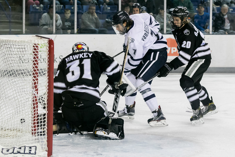 UNH's Brendan Van Riemsdyk, center, has his shot blocked wide by Providence goalie Hayden Hawkey, left, during Saturday's game at the Whittemore Center Arena in Durham. Photo by Scott Patterson/Fosters.com