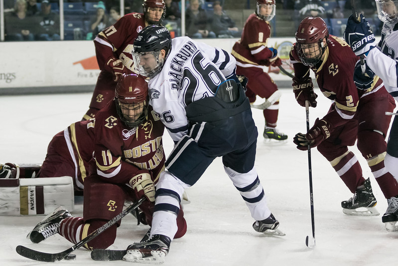 UNH's Liam Blackburn, center, fights for a loose puck in front of the BC goal during Friday night's Hockey East game at the Whittemore Center Arena in Durham.  Photo by Scott Patterson/Fosters.com