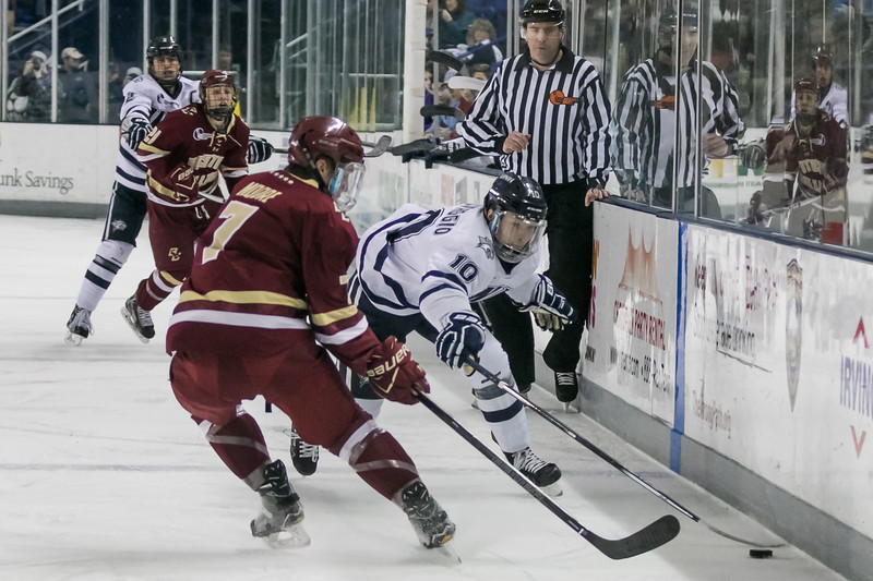 UNH's Jason Salvaggio, right, pushes the puck past BC's Connor Moore, left, during Friday night's Hockey East game at the Whittemore Center Arena in Durham.  Photo by Scott Patterson/Fosters.com