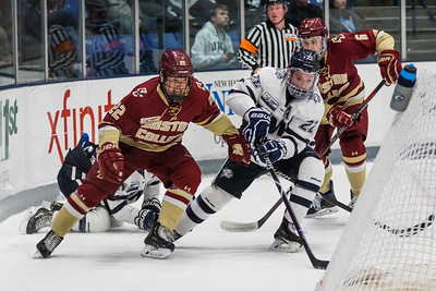 UNH's Aran Nazarian (22) looks to take a shot while being defended by BC's Aapeli Rasanen (22) during Hockey East action Saturday night in Durham. [Scott Patterson/Fosters.com]