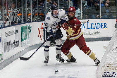 UNH's Frankie Cefalu (9) passes the puck while being defended by BC's Michael Kim (4) during Hockey East action Saturday night in Durham. [Scott Patterson/Fosters.com]