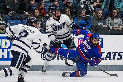 New Hampshire's Richard Boyd (15) and Lowell's Colin O'Niell battle along the boards during Hockey East action in Durham Friday. [Scott Patterson/Fosters.com]