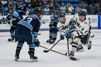 New Hampshire's Angus Crookshank (6) has his shot blocked by Maine's Rob Mitchel during Hockey East action in Durham Friday. [Scott Patterson/Fosters.com]