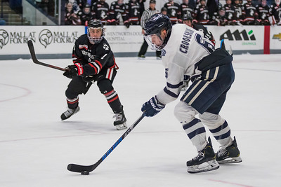 New Hampshire's Angus Crookshank (6) moves the puck as Northeastern's John Picking closes during Hockey East action in Durham Friday. [Scott Patterson/Fosters.com]