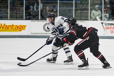 New Hampshire's Frankie Cefalu (9) looks to pass as Northeastern's Jordan Harris defends during Hockey East action in Durham Friday. [Scott Patterson/Fosters.com]
