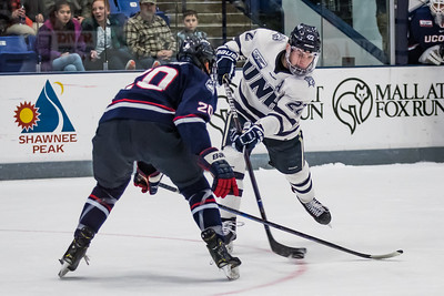 New Hampshire's Are Nazarian (22) slips a pass under the stick of Connecticut's Patrick Grasso (20) during Hockey East action in Durham Saturday. [Scott Patterson/Fosters.com]