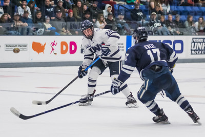UNH's Benton Maass (28) looks to pass while Yale's Kevin O'Niel (17) defends during hockey action in Durham Saturday. [Scott Patterson/ Fosters.com]
