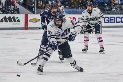 UNH's Patrick Grasso (20) takes a shot while being defended by Yale's Justin Pearson (18) during hockey action in Durham Saturday. [Scott Patterson/ Fosters.com]