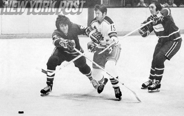 Two Vancouver Canucks team up on the Rangers Jean Ratelle. 1974
