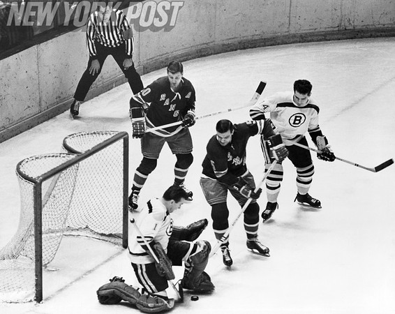 New York Rangers and Boston Bruins battle in front of the goal.