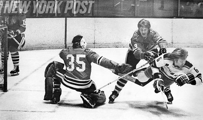 Two Chicago Blackhawk's team up on Ranger Glen Sather. 1973