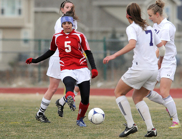 "Centaurus High School's Shanlie Anderson, No. 5, passes the ball past Holy Family's Makayla Welhelm, No. 7, on Monday, March 19, during a soccer game at Holy Family High School in Broomfield. For more photos of the game go to  <a href=""http://www.dailycamera.com"">http://www.dailycamera.com</a><br /> Jeremy Papasso/ Camera"