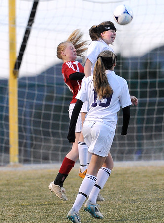 """Holy Family High School's Abby Metzger, heads the ball over Centaurus High School's Morgan Brendefur, back left, on Monday, March 19, during a soccer game at Holy Family High School in Broomfield. For more photos of the game go to  <a href=""""http://www.dailycamera.com"""">http://www.dailycamera.com</a><br /> Jeremy Papasso/ Camera"""