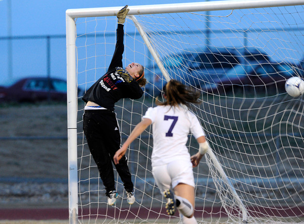 "Centaurus High School goalkeeper Kelly Turcotte jumps and misses the save kicked by Holy Family High School's Micaela Blanchard, No. 24, not pictured, while Makayla Welhelm, No. 7, runs in to make sure it's a goal on Monday, March 19, during a soccer game at Holy Family High School in Broomfield. For more photos of the game go to  <a href=""http://www.dailycamera.com"">http://www.dailycamera.com</a><br /> Jeremy Papasso/ Camera"