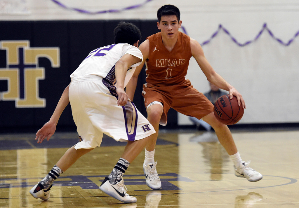 . Mead High School\'s Cameron Cheung dribbles past Aaron Sanders during a game against Holy Family on Tuesday in Broomfield. More photos: www.BoCoPreps.com Jeremy Papasso/ Staff Photographer/ Feb. 14, 2017