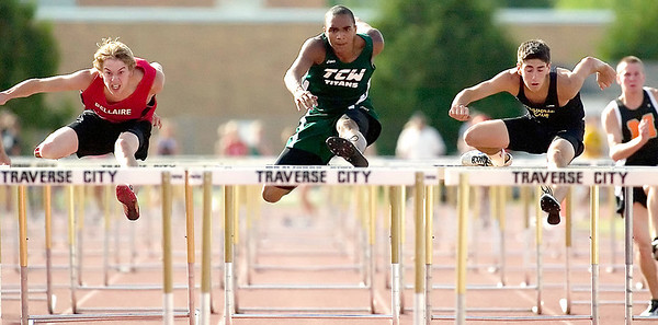 Record-Eagle/Jan-Michael Stump<br /> From left, Bellaire's Donavan Dawson (second place), Traverse City West's Cody Russell (third) and Traverse City Central's Spencer Potter (first) run the 110 high hurdles.