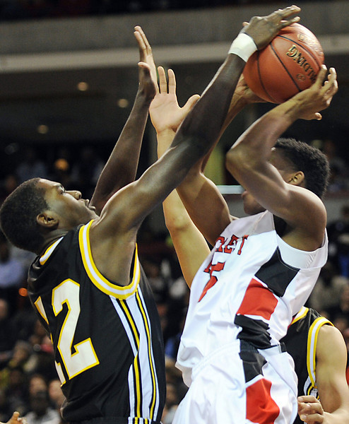 Irmo's Javis Howard (12) defends against Hillcrest's Tre Smith (15). Irmo beat Hillcrest 63-49 to advance to Friday's Class  AAAA State Championship game against Goose Creek at the Colonial Life Center in Columbia. <br /> The Hillcrest Rams and the Irmo Yellow Jackets battled in the Upper State Basketball Championships at the Bi-Lo Center in Greenville.<br /> GWINN DAVIS PHOTOS<br /> gwinndavisphotos.com (website)<br /> (864) 915-0411 (cell)<br /> gwinndavis@gmail.com  (e-mail) <br /> Gwinn Davis (FaceBook)