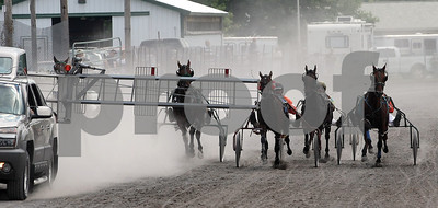 Spencer Tulis / Finger Lakes Times A cloud of dust trails the vehicle holding the starting gate for harness racing at the Seneca County Fairgrounds Monday. The Standardbred horse racing is one of the events that kicks off the Seneca County Fair each year. The winner of this race of two year old pacers was Betterwalkthewalk (third from right).