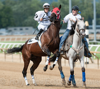 Real Luck gives jockey Crystal Carman and the outrider a hard time in the post parade for the 6th race of the West Virginia Derby day card