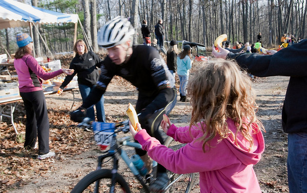 Record-Eagle/Douglas Tesner<br /> <br /> Rebecca Boynton, 7, hands out fruit at a check point near Williamsberg Road as Luke Asborn speeds by during the Iceman Cometh Challenge Bike Race