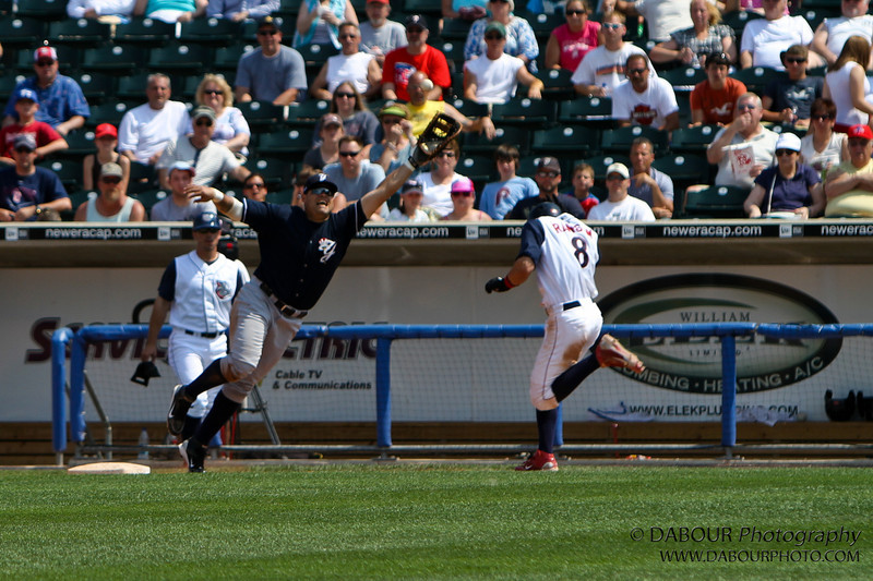 The ball is hard to see. It's about a foot above his glove just to the right of the man's head with the yellow shirt. The throw was wide. IronPigs-183