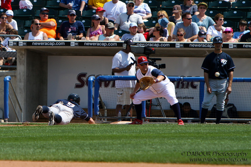 The ball is over the belly button of the first base coach. Don't worry no coach's were harmed in the making of this photograph :)<br /> IronPigs-170
