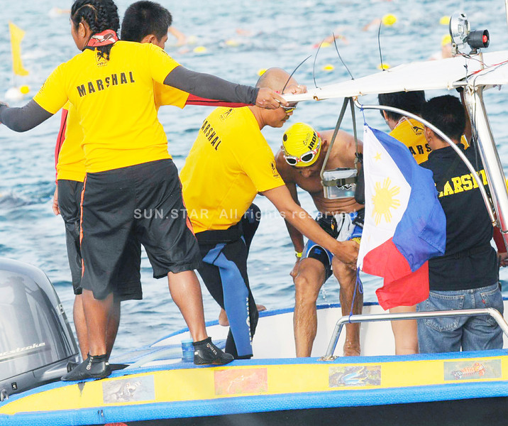 RESCUE. Marshals help a swimmer to a see an ambulance after struggling against the big waves. (Sun.Star Photo/Allan Cuizon)
