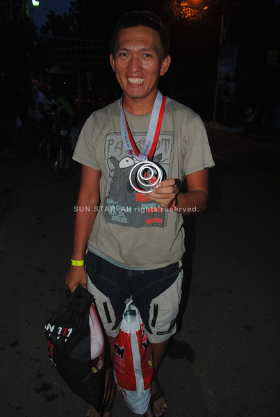 CEBU. Caresharing Inc.'s Jason Durado shows the medal he got after finishing the race at 6:15:58.