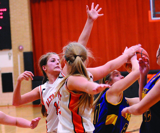 A pair of Altamont defenders converge on the Carlyle offense in the Lady Indians loss.
