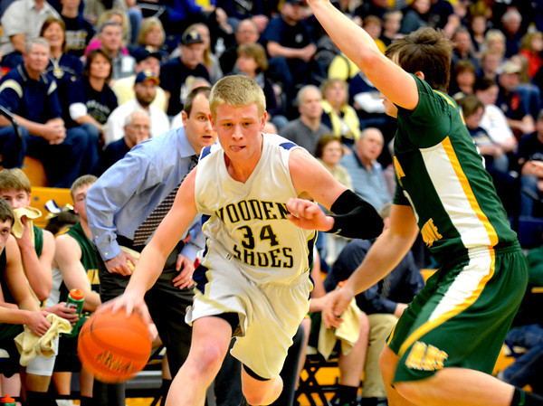 Teutopolis' Reed Hardiek fends off some tight defense from Mattoon's Andy Vieth during the Wooden Shoes' loss to the Green Wave.