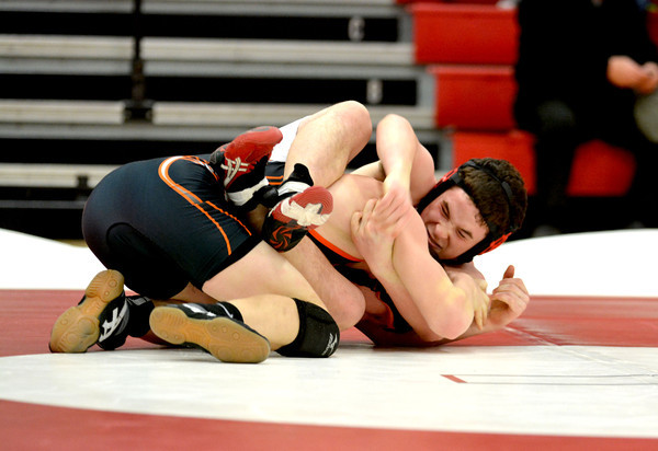 Effingham's Alex Artola works for position while holding Olney's Dalyn Brach to the mat during the 144-pound bout.