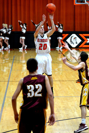 Altamont's Garrett Ziegler rises up for a 3-pointer while Dieterich's Lance Niemerg (32) and Alex Bohnhoff (right) defend at the National Trail Conference tournament.