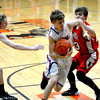 St. Anthony's Neil Williams shields the ball from a Neoga defender while driving into the lane during St. Anthony's semifinal win at the National Trail Conference tournament.
