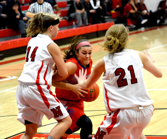 St. Anthony's Makayla Walsh looks to split a double team between Neoga's EC Thies (14) and Kelli Erickson (21) during the Bulldogs' win.