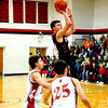 Justin McGinnis goes for a jumper over the defense of two players from North Clay.