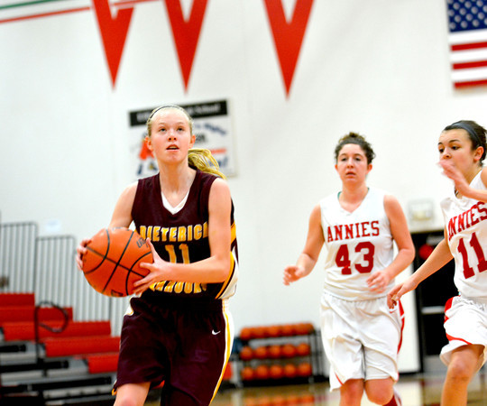 Dieterich's Courtney Flach finishes off a fast break with an open layup as a pair of Centralia defenders trail the play at the Effingham Round Robin tournament.