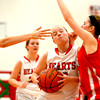 Effingham's Caitlin Kaufman drives to the basket and is fouled by Neoga's Olivia Ott (right) during the fourth quarter of Effingham's win over Neoga at the Effingham Round Robin Tournament.