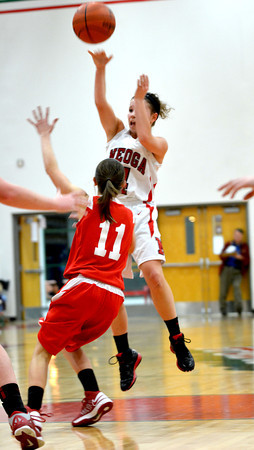 Neoga's Madison Butler throws a jumping pass over the defense of Centralia's Abby Ingenrieth (11).